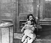 Girl Sitting on Doorstep with Baby on Her Lap